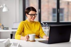 Aff?rskvinnan med b?rbara datorn dricker kaffe p? kontoret royaltyfri fotografi