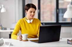 Aff?rskvinnan med b?rbara datorn dricker kaffe p? kontoret royaltyfri foto