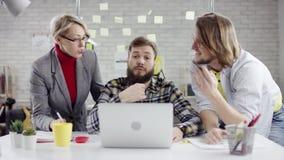 Aff?rslag av ungdomarsom tycker om att arbeta tillsammans, millennialsgrupp som talar ha gyckel i det hemtrevliga kontoret som ?r stock video
