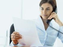 Aff?rsledare som arbetar i kontoret och g?r p?ringningar royaltyfri fotografi