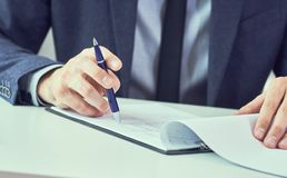 Aff?rsman som l?ser det uthyrnings- avtalet, innan framst?llning av ett avtal F?retags man med pennan i handen som arbetar i mode arkivbilder