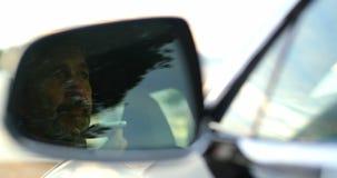 Aff?rsman som talar p? mobiltelefonen i en bil 4k arkivfilmer