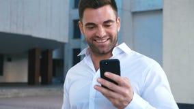 Aff?rsman Using Smartphone och reagera till framg?ng Stiligt yrkesmässigt lyckat nå för affärsman som är personligt arkivfilmer