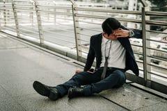 Aff?rsmanarbetsl?ns fr?n f?retagssammantr?de p? gatan och hans handen kn?ppte fast huvud, ?r han mening av stressat och sorgsenhe royaltyfri bild