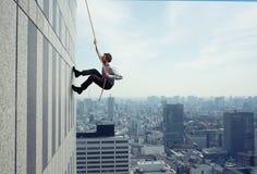 Aff?rsmannen kl?ttrar en byggnad med ett rep Begrepp av beslutsamhet royaltyfria bilder