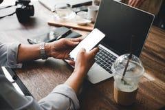 Aff?rsmannen som anv?nder mobilen, och b?rbara datorn finner ett jobb i coffee shop arkivfoto