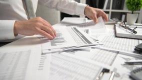 Aff?rsmannen som arbetar p? kontoret och ber?knar finans, l?ser och skriver rapporter begrepp f?r finansiell redovisning f?r aff?