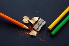 Affûteuse et crayons colorés sur le noir Photos libres de droits