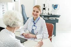 Affable glance of female doctor. Cheerful ophthalmologist is looking at patient with kind smile and listen to old woman. Portrait Stock Photos