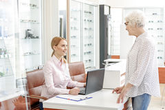 Affable glance of female shop advisor. Old women is standing near countertable and talking to receptionist in glasses shop. Young lady looking at customer with Stock Photo