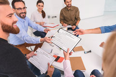 Affable man giving forms to people. Smiling psychologist is surrendering documents with personal information. Group of cheerful people sitting at table Royalty Free Stock Photos
