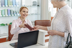 Affable receptionist giving glasses to customer. Old women is taking brown cover of eyeglasses with order from happy smiling secretary. Portrait Royalty Free Stock Photo