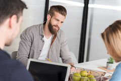 Affable smiling bearded manager among co-workers. Peaceful office worker is sitting afore his colleagues near table and looking at them with light smile Stock Photography