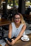 Affaires élégantes femelles dans un café extérieur avec le téléphone portable image stock