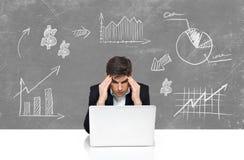 Affaires avec la séance de réflexion d'homme d'ordinateur portable Photo stock