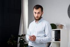 Affaires de bureau de thème Jeune homme caucasien beau sûr et fort avec la barbe se tenant dans la chambre lumineuse sur le lieu  images stock