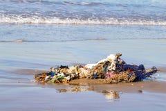 Affaires de déchets, d'habillement et de ménage délogées de l'Océan Atlantique sur la plage d'Agadir, Maroc, Afrique image libre de droits