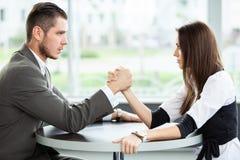 Affaires et concept de bureau - bras de fer de femme d'affaires et d'homme d'affaires au cours de la réunion dans le bureau image stock