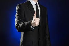Affaires et la présentation du thème : homme dans un costume noir montrant des gestes de main sur un fond bleu-foncé dans le stud Image libre de droits
