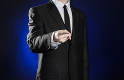 Affaires et la présentation du thème : homme dans un costume noir montrant des gestes de main sur un fond bleu-foncé dans le stud Images libres de droits