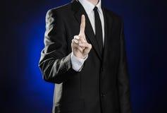 Affaires et la présentation du thème : homme dans un costume noir montrant des gestes de main sur un fond bleu-foncé dans le stud Photographie stock libre de droits