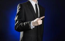 Affaires et la présentation du thème : homme dans un costume noir montrant des gestes de main sur un fond bleu-foncé dans le stud Images stock