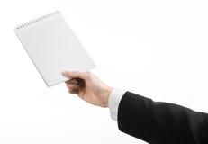 Affaires et sujet de journaliste : la main d'un journaliste dans un costume noir tenant un carnet avec un crayon sur un fond blan Photographie stock libre de droits