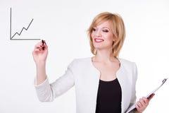 Affaires, finances et sciences économiques - jeune femme d'affaires attirante écrivant un graphique Femelle sur le fond blanc Photos stock