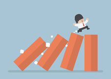 Affaires fonctionnant sur renverser le domino illustration stock