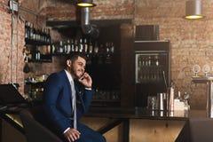 Affaires gaies parlant au téléphone dans la barre Photographie stock libre de droits