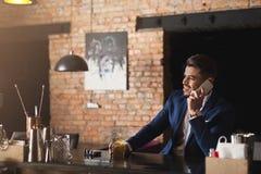Affaires gaies parlant au téléphone dans la barre Photo libre de droits