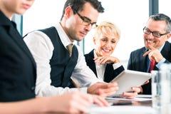 Affaires - réunion dans le bureau, équipe travaillant avec le comprimé Photographie stock libre de droits