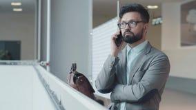 Affaires sur l'aller L'homme se tient en longueur à l'appareil-photo avec le smartphone banque de vidéos