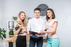 Affaires, travail d'équipe et associations de thème Un groupe des jeunes, trois personnes, support dans un bureau près de la tabl images stock