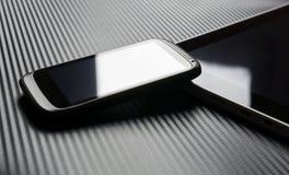 Affaires vides Smartphone avec la réflexion se penchant sur la Tablette avec le fond de carbone Image stock