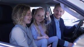 Affare automatico, mamma e papà sorridente felice con la chiave d'ondeggiamento dell'automobile della famiglia di rassegne della