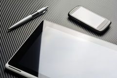 Affare in bianco Smartphone e Pen Lying Next To una compressa con la riflessione sopra un fondo del carbonio Fotografia Stock Libera da Diritti