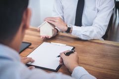 Affare che firma una casa compra-vendita del contratto, agente di assicurazione Immagine Stock