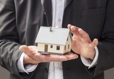 Affare dell'agente di agente immobiliare con la casa in mani Immagine Stock