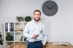 Affare dell'ufficio di tema Giovane uomo caucasico bello sicuro e forte con la barba che sta nella stanza luminosa sul posto di l immagini stock