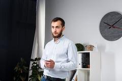 Affare dell'ufficio di tema Giovane uomo caucasico bello sicuro e forte con la barba che sta nella stanza luminosa sul posto di l fotografie stock