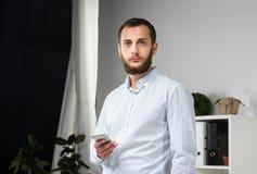 Affare dell'ufficio di tema Giovane uomo caucasico bello sicuro e forte con la barba che sta nella stanza luminosa sul posto di l fotografia stock