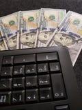 Affare di Internet, tastiera numerica circondata da 100 banconote in dollari Immagine Stock