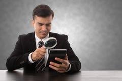 Affare di ricerca della lente d'ingrandimento di uso dell'uomo d'affari immagini stock libere da diritti