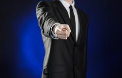 Affare e la presentazione del tema: uomo in un vestito nero che mostra i gesti di mano su un fondo blu scuro nello studio isolato Immagine Stock