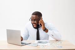 Affare e successo Riuscito uomo afroamericano bello che indossa vestito convenzionale, facendo uso del computer portatile per dis immagini stock