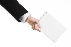 Affare ed argomento del reporter: la mano di un giornalista in un vestito nero che tiene un taccuino con una matita su un fondo b Immagine Stock Libera da Diritti