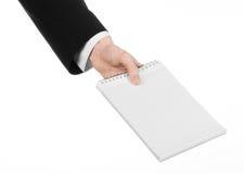 Affare ed argomento del reporter: la mano di un giornalista in un vestito nero che tiene un taccuino con una matita su un fondo b Immagini Stock Libere da Diritti