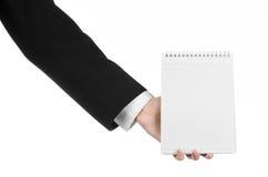 Affare ed argomento del reporter: la mano di un giornalista in un vestito nero che tiene un taccuino con una matita su un fondo b Immagine Stock