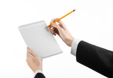 Affare ed argomento del reporter: la mano di un giornalista in un vestito nero che tiene un taccuino con una matita su un fondo b Fotografia Stock